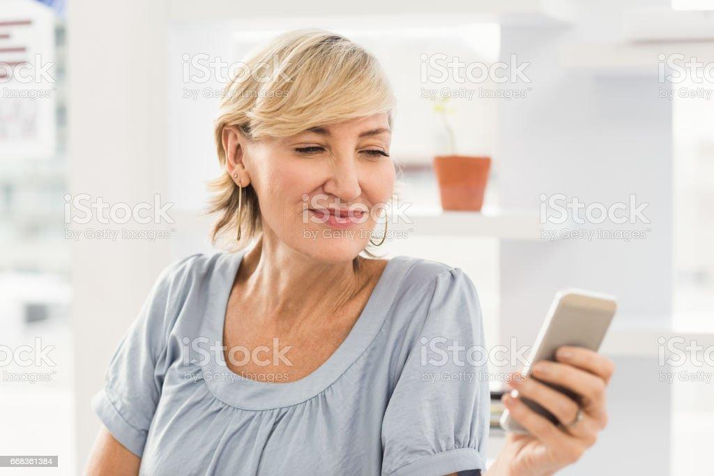 Smiling businesswoman sending a text stock photo