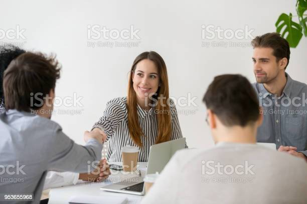 Smiling businesswoman shaking hand of male partner at group meeting picture id953655968?b=1&k=6&m=953655968&s=612x612&h=9cwygmiw9nalr32cbudieyiccezxk58xtobmr1cquvq=