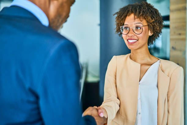 Smiling businesswoman shaking hands with her manager in an office stock photo