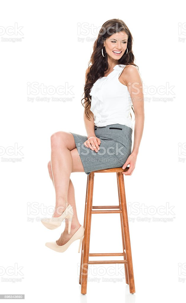Smiling businesswoman sitting on stool royalty-free stock photo