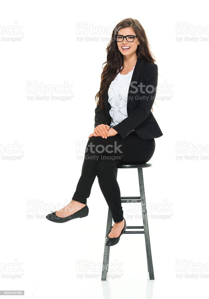 Smiling businesswoman sitting on stool stock photo