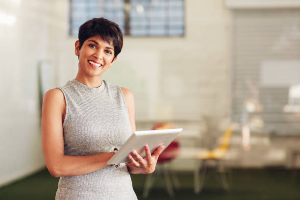 Smiling businesswoman standing in an office working on her tablet stock photo
