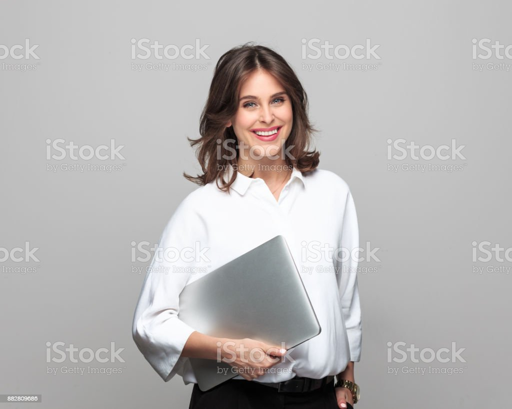 Smiling businesswoman standing with a laptop Portrait of smiling businesswoman standing with a laptop crossed against grey background. 25-29 Years Stock Photo