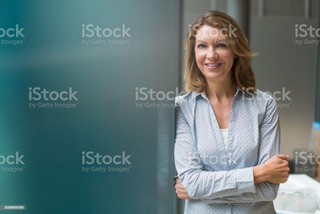 Lächelnd Geschäftsfrau stehend mit Arme verschränkt  – Foto