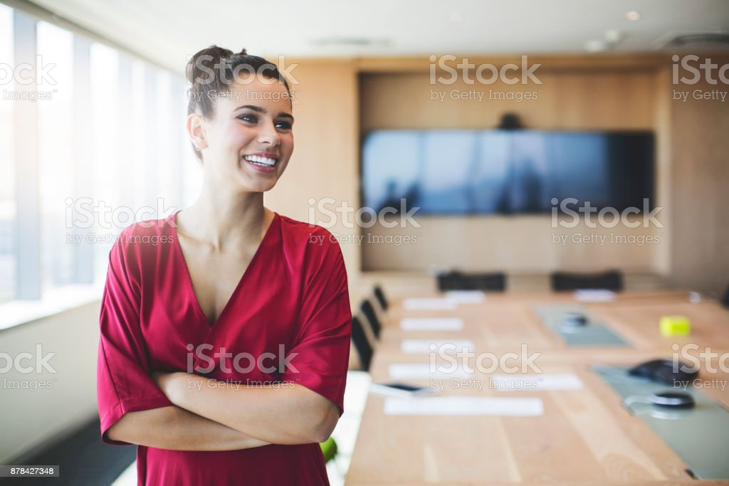 Smiling businesswoman standing with arms crossed stock photo
