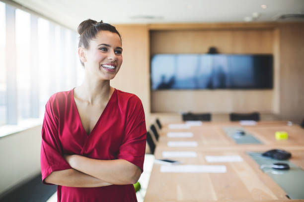 smiling businesswoman standing with arms crossed - selective focus stock pictures, royalty-free photos & images