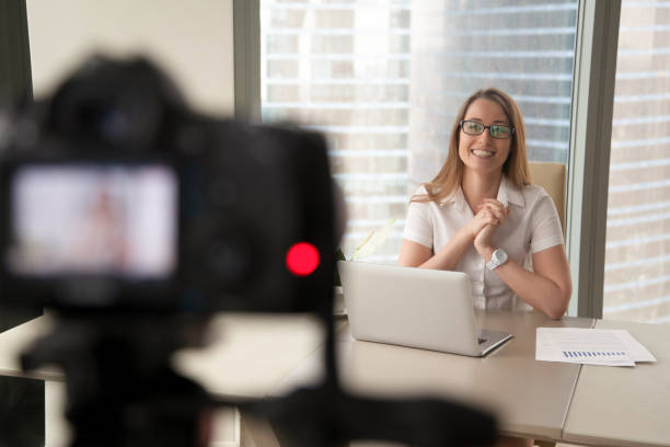 Smiling businesswoman talking on camera, lady recording business video blog stock photo