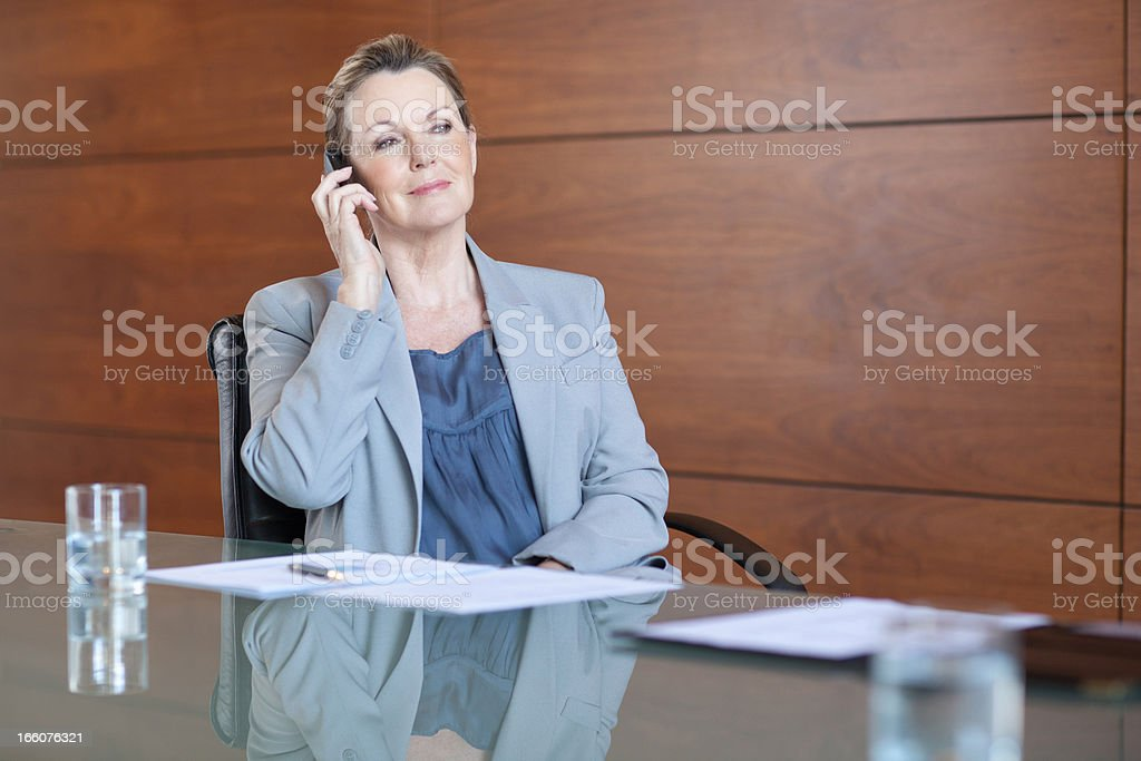 Smiling businesswoman talking on cell phone in conference room royalty-free stock photo