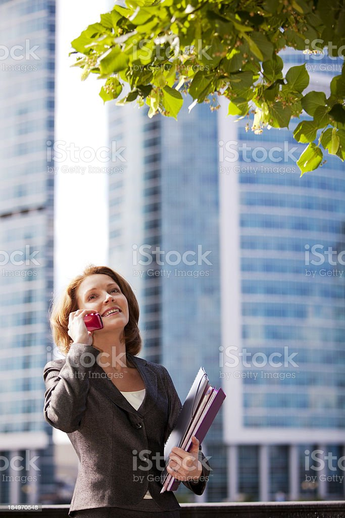 Smiling businesswoman talking on mobile phone outdoors royalty-free stock photo
