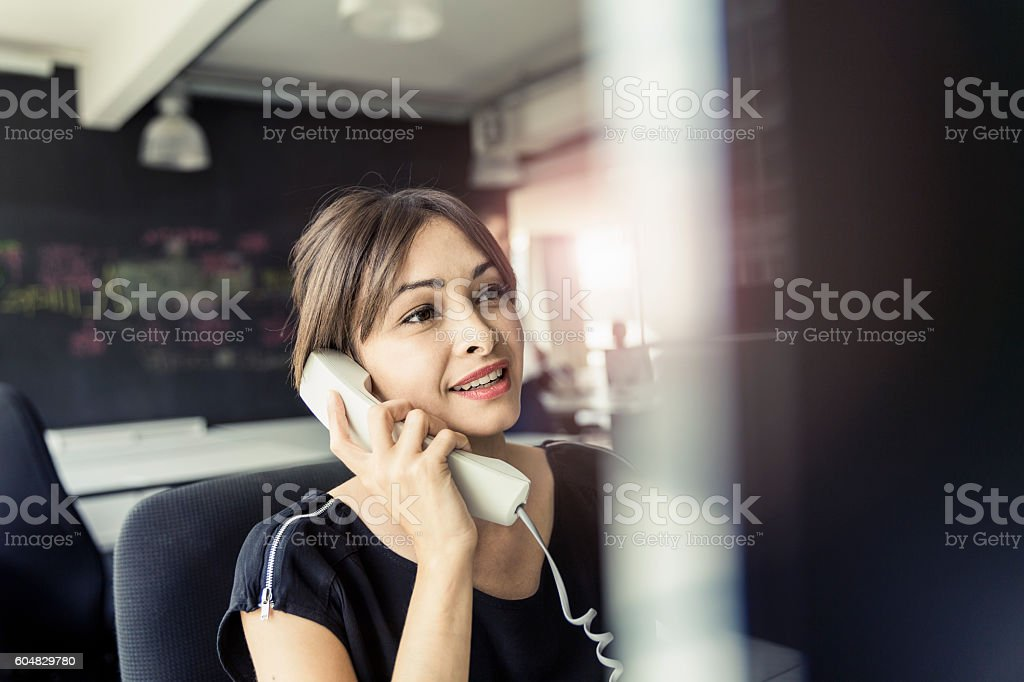 Smiling businesswoman talking on phone in office stock photo