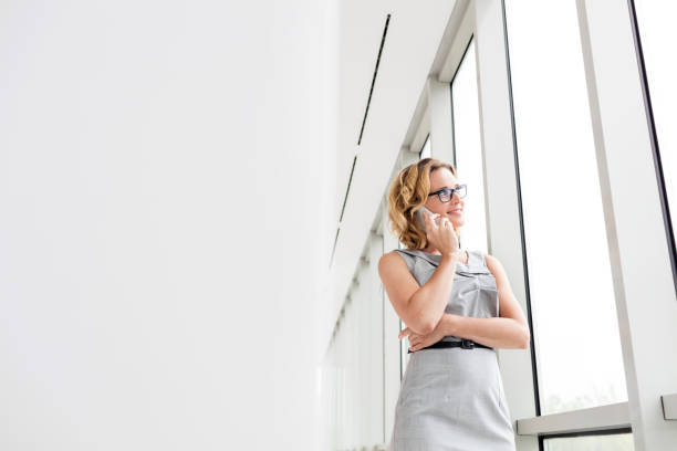 Smiling businesswoman talking on smartphone at new office stock photo