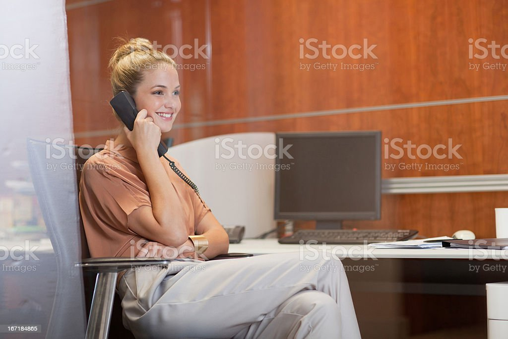 Smiling businesswoman talking on telephone in office stock photo