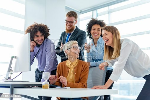 956725740istockphoto Smiling businesswoman talking to colleagues in a meeting room 1157376044
