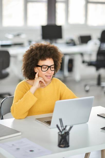 Lächelnde Geschäftsfrau mit Laptop im modernen Büro. – Foto