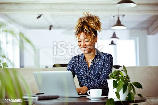istock Smiling businesswoman using laptop in office 1207095853