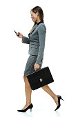 Smiling businesswoman using mobile and walkinghttp://www.twodozendesign.info/i/1.png