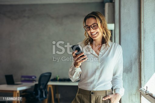 Smiling businesswoman using phone in office. Small business entrepreneur looking at her mobile phone and smiling.