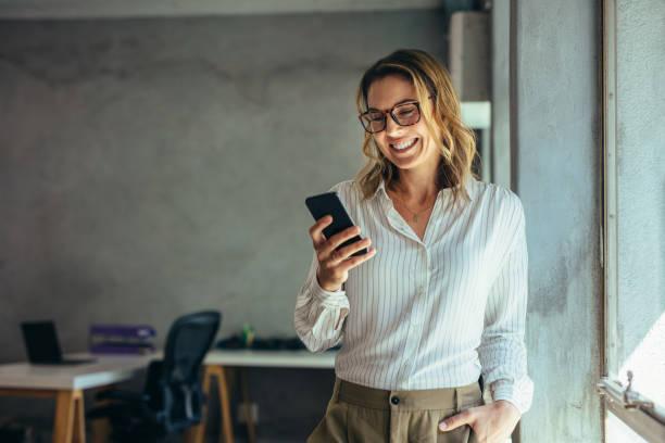 imprenditrice sorridente che usa il telefono in ufficio - dispositivo informatico portatile foto e immagini stock