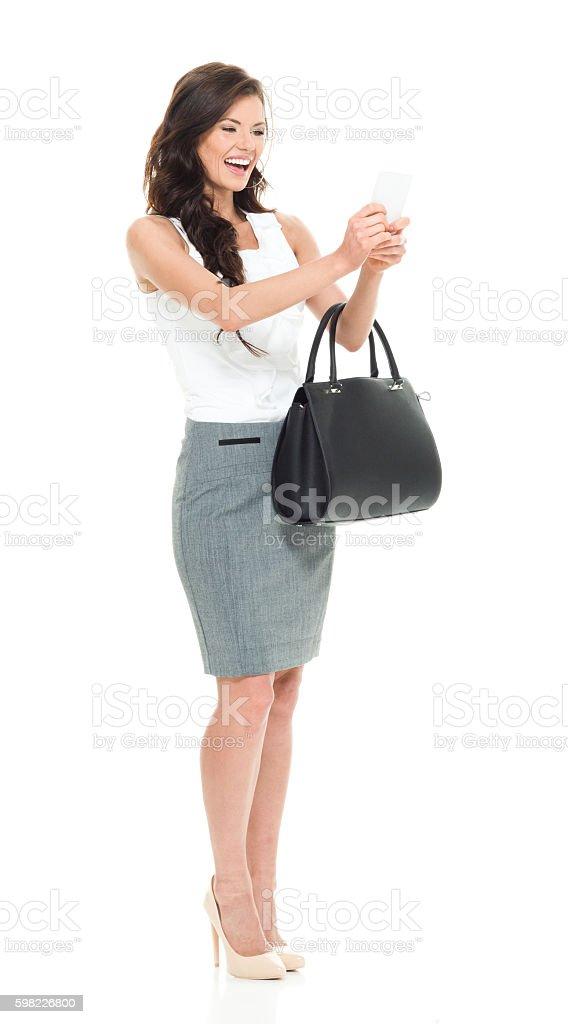 Mulher de negócios sorridente usando telefone foto royalty-free