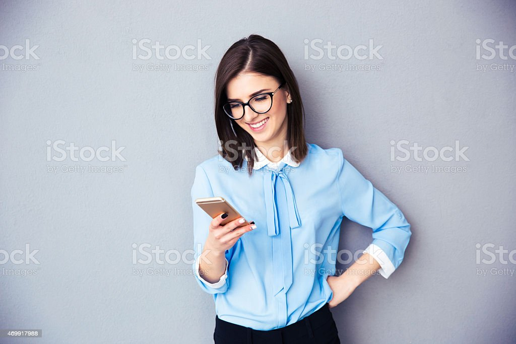 Smiling businesswoman using smartphone on gray background stock photo