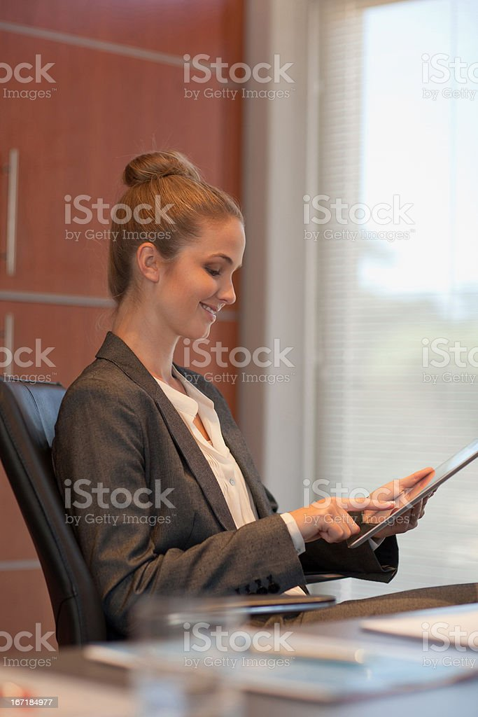 Smiling businesswoman using tablet at desk in office royalty-free stock photo