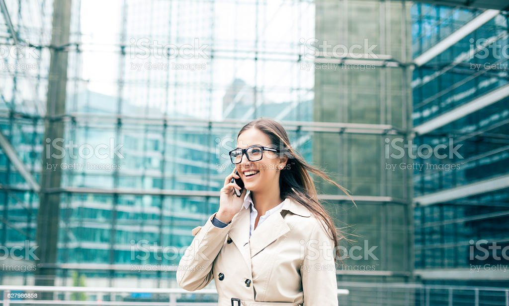 Young bussineswoman walking on street and talking on smart phone....