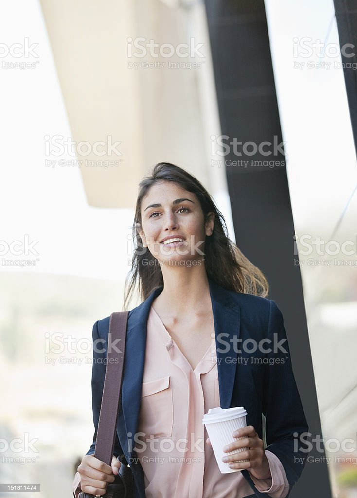 Smiling businesswoman walking with coffee cup stock photo