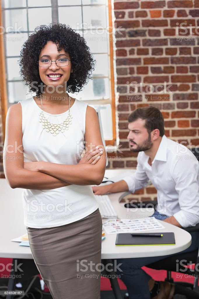 Smiling businesswoman with arms crossed in office stock photo