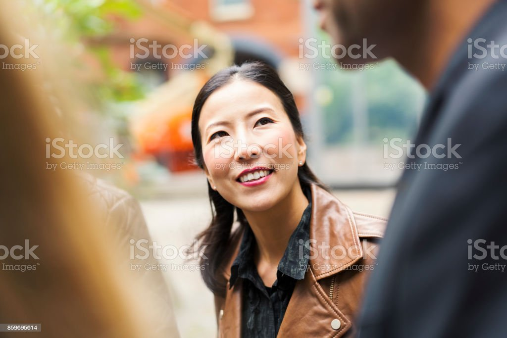 Smiling businesswoman with coworkers in office stock photo