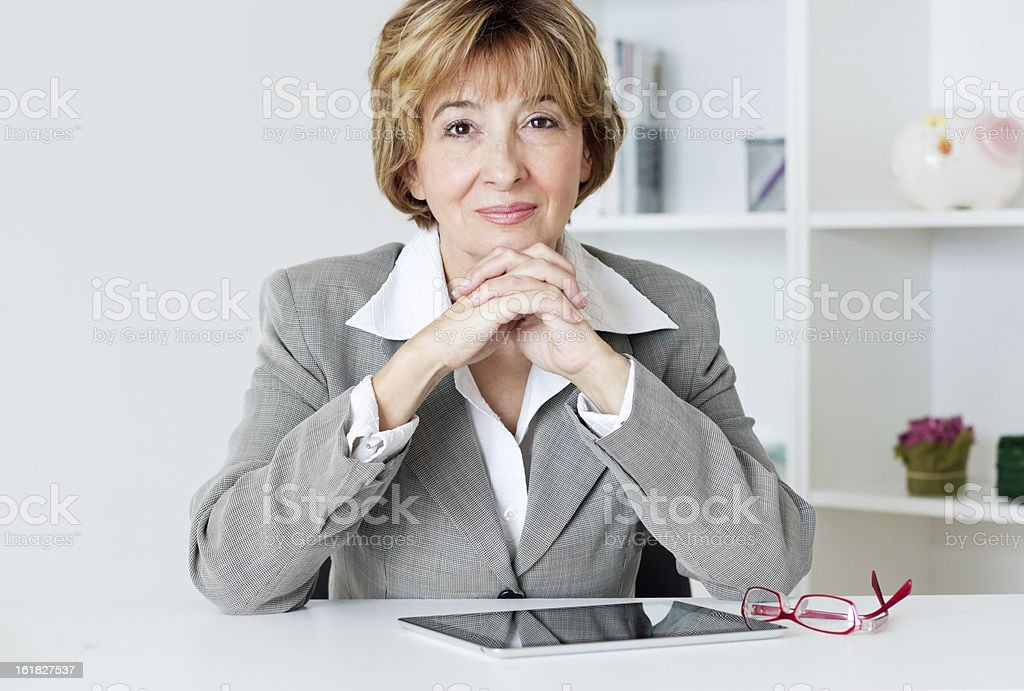 Smiling businesswoman with hands intertwined under her chin stock photo