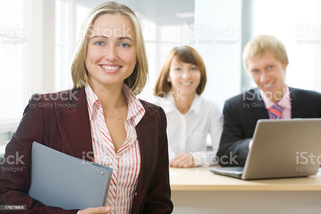 A smiling businesswoman with her smiling team royalty-free stock photo
