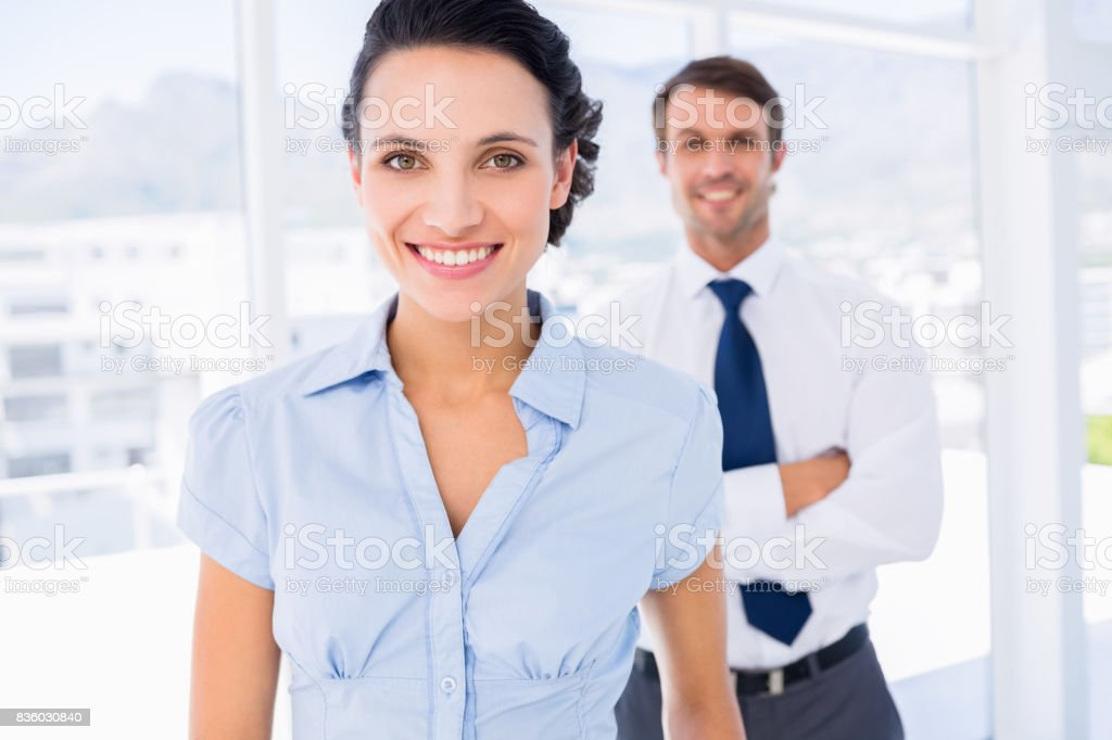 Smiling businesswoman with male colleague in background stock photo