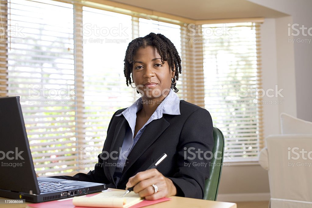 Smiling businesswoman with pen and laptop royalty-free stock photo