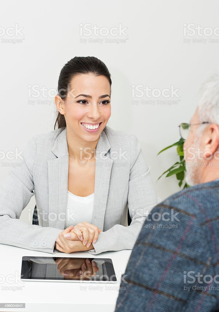 Smiling businesswoman with tablet consulting with man stock photo