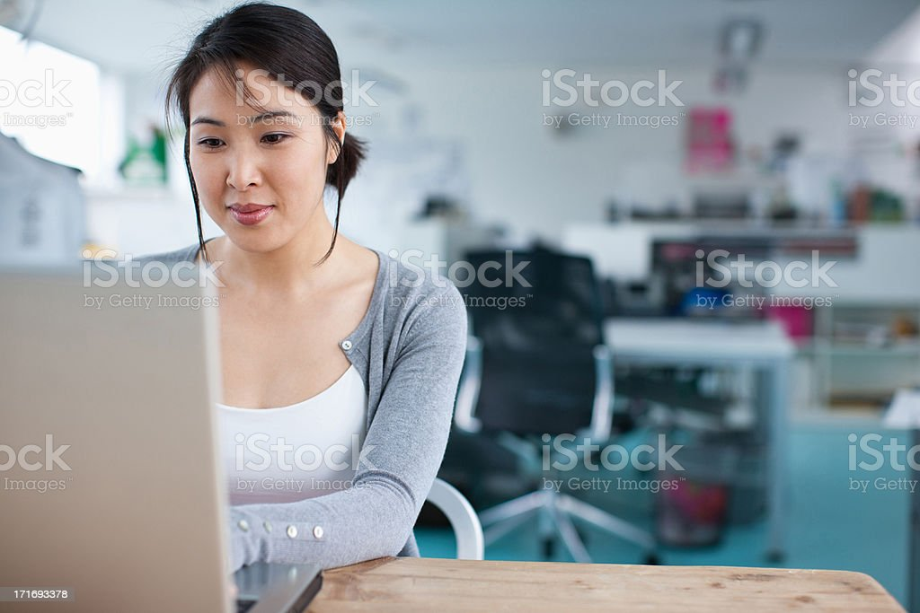 Smiling businesswoman working at laptop in office stock photo