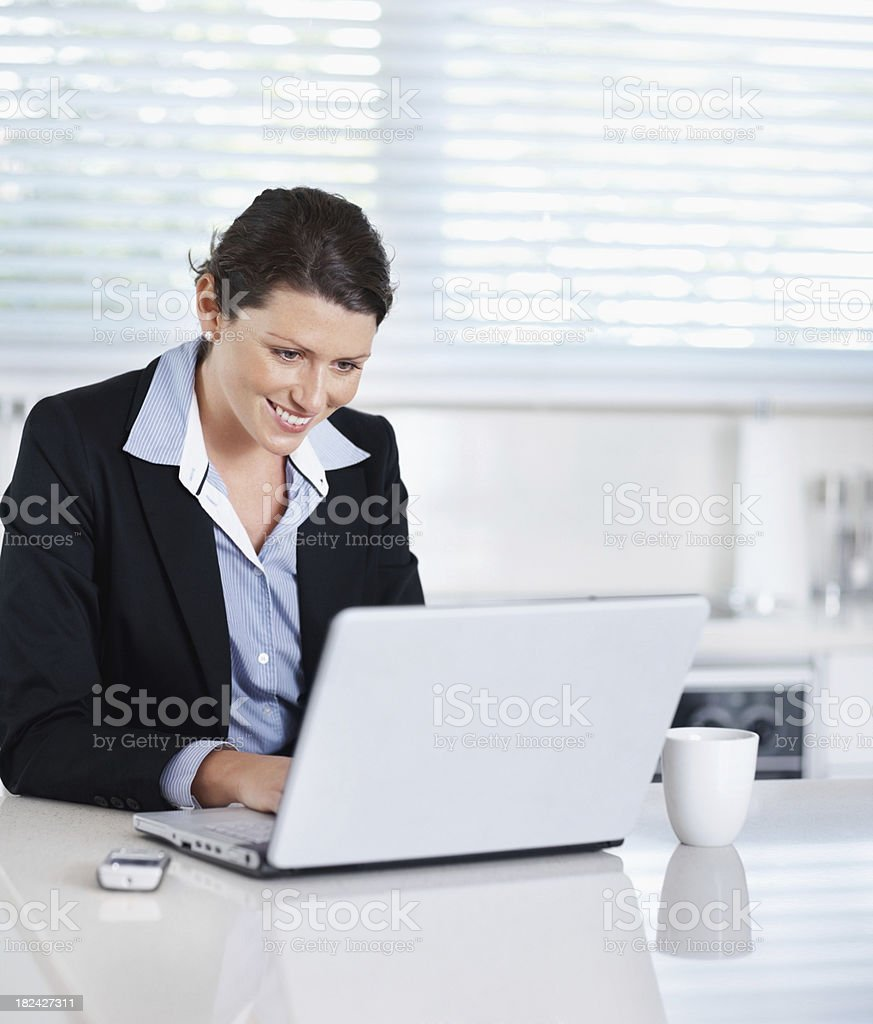 Smiling businesswoman working on laptop in office royalty-free stock photo