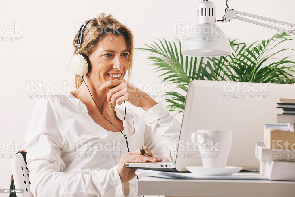 Smiling businesswoman working with laptop at home stock photo