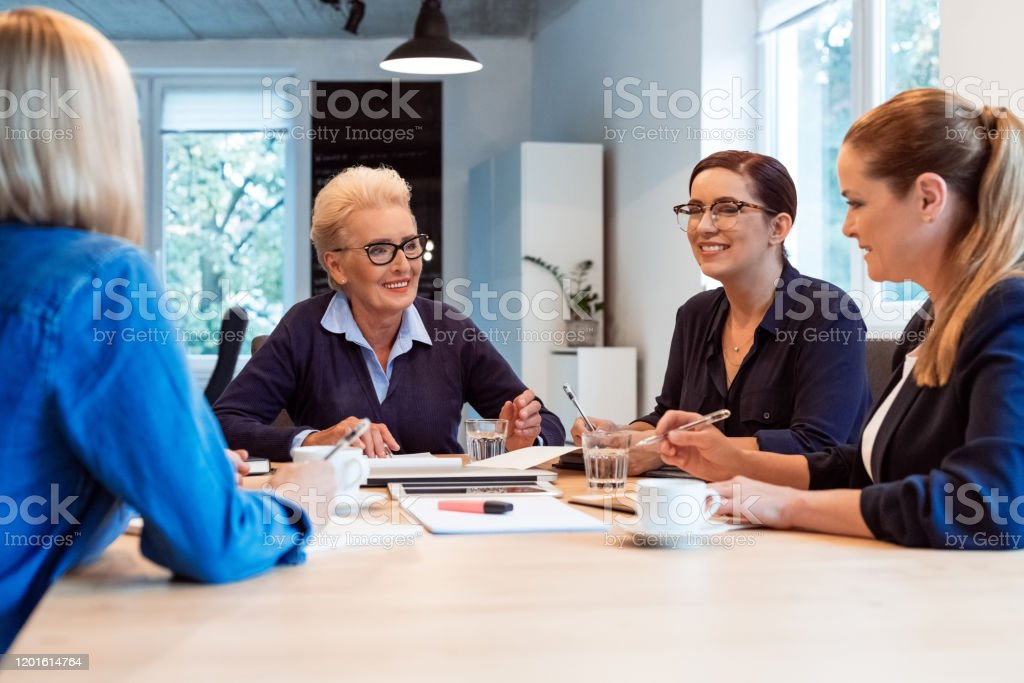 Smiling businesswomen discussing in office meeting Smiling female professionals discussing in meeting. Senior businesswoman planning with colleagues. They are running start up business. 35-39 Years Stock Photo