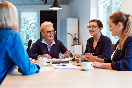 Smiling Businesswomen Discussing In Office Meeting Stock Photo - Download Image Now