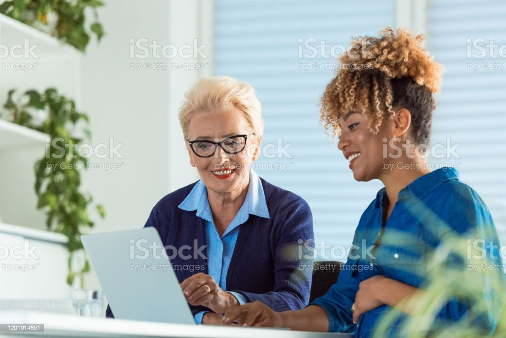 Smiling businesswomen discussing over laptop Smiling female professionals discussing over laptop. Senior businesswoman sitting with pregnant colleague at desk in office. They are working over new business. 35-39 Years Stock Photo