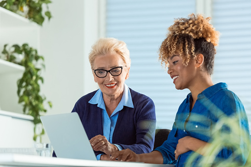 Smiling Businesswomen Discussing Over Laptop Stock Photo - Download Image Now