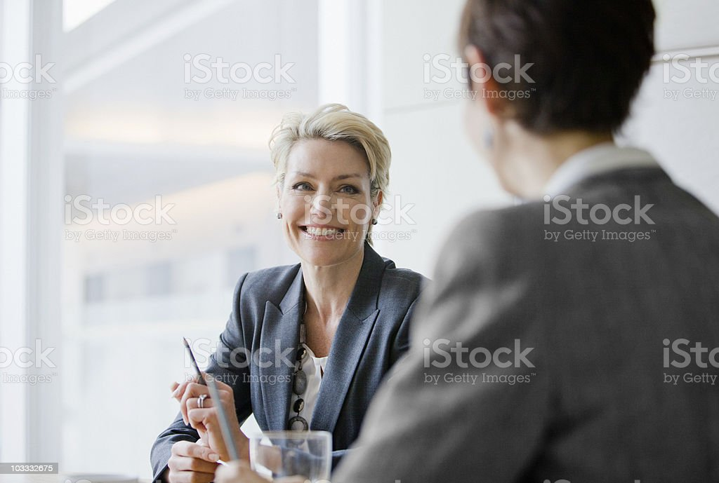 Smiling businesswomen in meeting stock photo