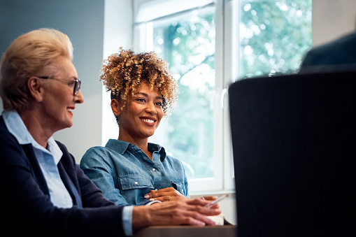 Smiling Businesswomen Looking Away In Office Stock Photo - Download Image Now
