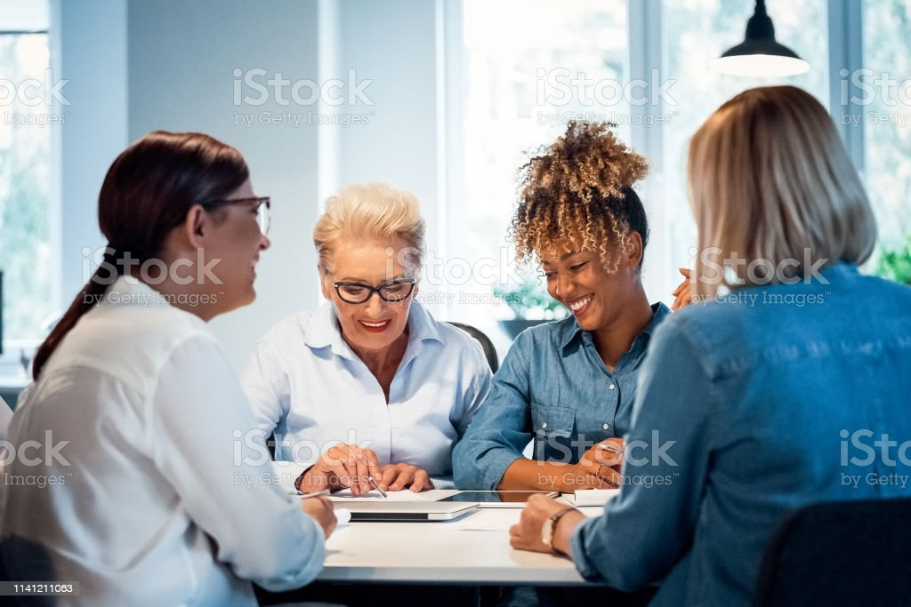 Smiling businesswomen working in new office Smiling businesswomen working at desk in new office. Confident female executives are planning strategies. Senior expertise is advising colleagues. 35-39 Years Stock Photo