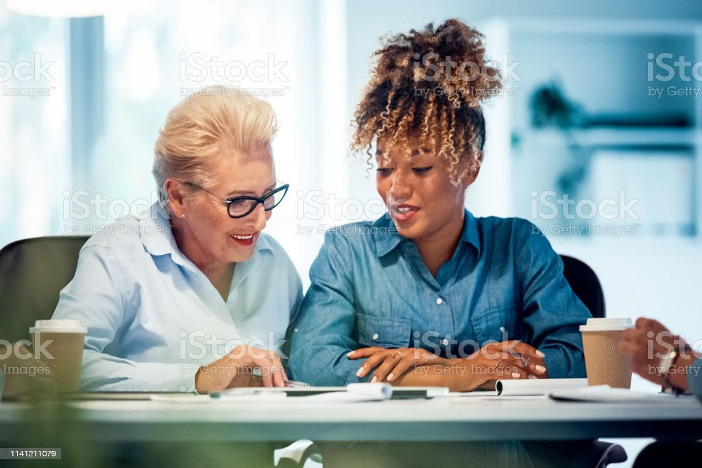 Smiling businesswomen working in new office Smiling businesswomen working at desk in new office. Confident female executives are planning strategies. Senior expertise is advising colleague. 35-39 Years Stock Photo