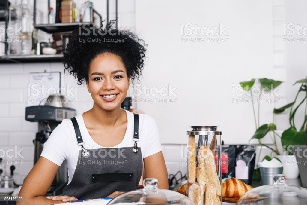 Smiling bussineswoman standing in her coffee shop and looking at camera stock photo