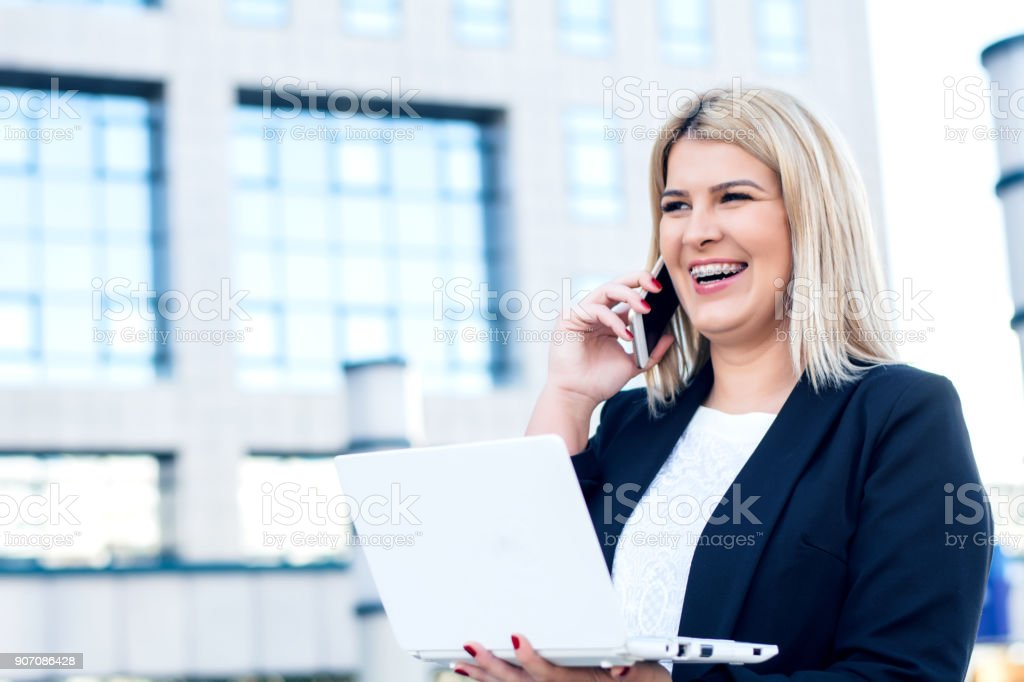 Smiling bussineswoman talking on the phone on street stock photo