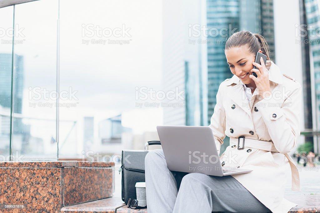 Smiling bussineswoman using laptop on street stock photo