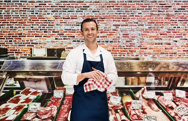 Souriant butcher en magasin - Photo