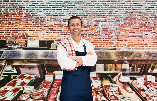 Smiling butcher standing in shop - Photo